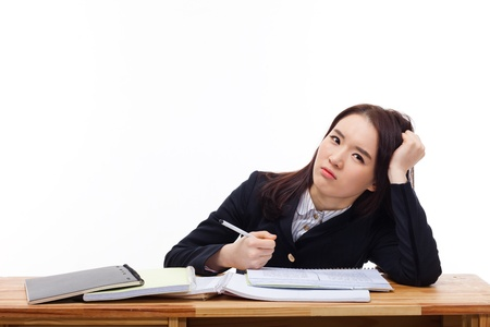 hard working woman: Young Asian student having trouble on the desk isolated on white background.  Stock Photo
