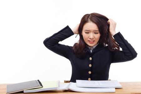 Jonge Aziatische student problemen op het bureau geïsoleerd op witte achtergrond.