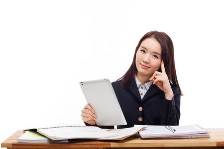 Jonge Aziatische student meisje met behulp van tablet-pc op het bureau op een witte achtergrond.