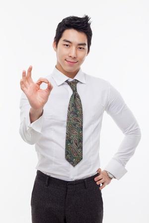 Jonge Aziatische zakenman toont ok teken geïsoleerd op een witte achtergrond.