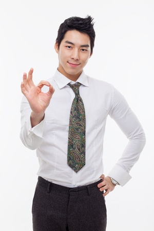 Young Asian business man showing okay sign isolated on white background.