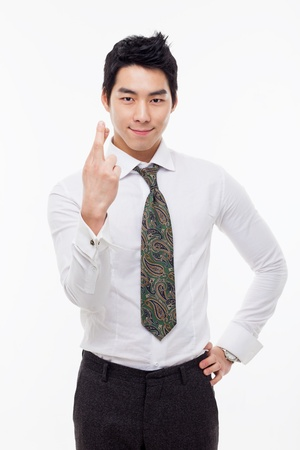 good looks: Young Asian business man showing lucky sign isolated on white background.