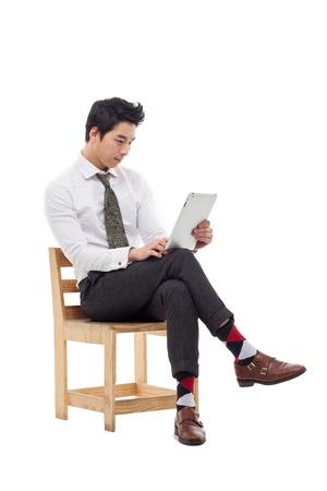 Jonge Aziatische zaken man met behulp van een pad PC zitten op de stoel geïsoleerd op een witte achtergrond. Stockfoto