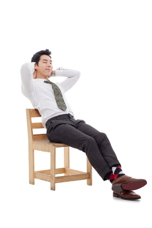 Thinking Young Asian business man sitting on the chair isolated on white background. Stock Photo - 17687001