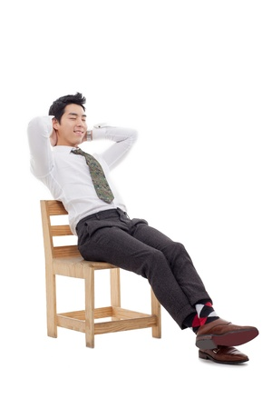 Thinking Young Asian business man sitting on the chair isolated on white background.  Stock Photo