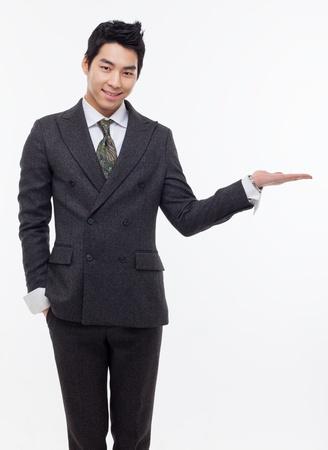 Jonge Aziatische zakenman blijkt iets geïsoleerd op een witte achtergrond. Stockfoto