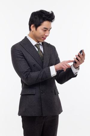 Aziatische zakenman met mobiele telefoon op een witte achtergrond. Stockfoto