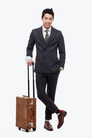 depart: Businessman walking along pulling some travel luggage isolated on white background.