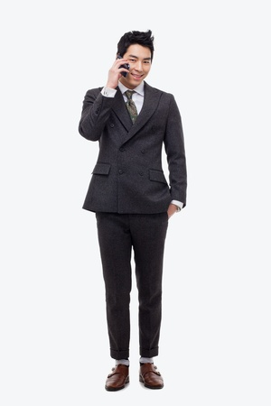 Asian business man with cellphone isolated on white background. Фото со стока