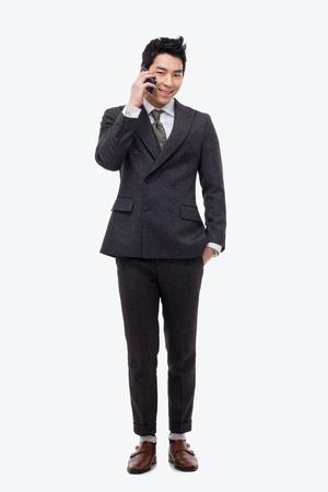 Aziatische business man met mobiele telefoon geïsoleerd op witte achtergrond.