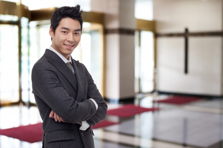 Young Asian business man in business background.