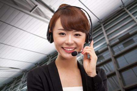 Lachende call center operator Aziatische zakelijke vrouw in zakelijke achtergrond. Stockfoto