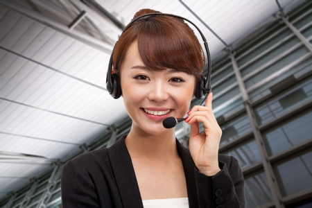 Smiling call center operator asian business woman in business background.  Stock Photo