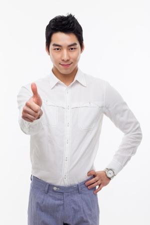Happy lachende jonge Aziatische man show duim geïsoleerd op een witte achtergrond.