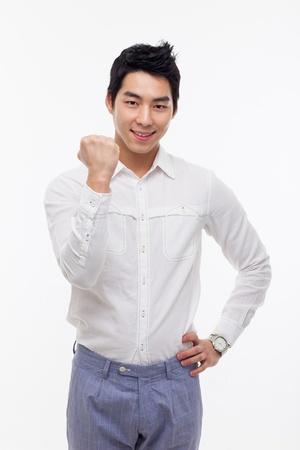 Jonge Aziatische mens die vuist en gelukkig teken geïsoleerd op witte achtergrond. Stockfoto