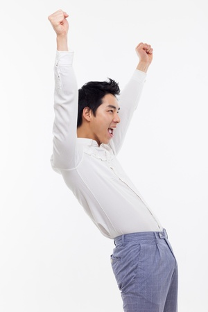 excited man: Young Asian man showing fist and happy sign isolated on white background.