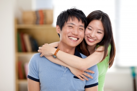 Happy young Asian couple isolated in home background. photo