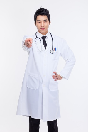 certitude: Young asian doctor pointing you isolated on white background.
