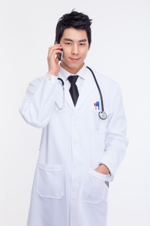 Young Asian doctor using smar phone isolated on white background. Stock Photo - 18193123