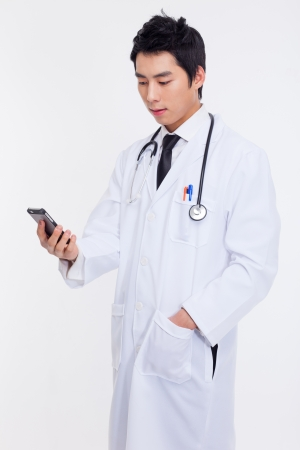 Young Asian doctor using smar phone isolated on white background. photo