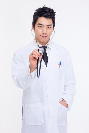 Jonge Aziatische arts met behulp van stethoscoop geïsoleerd op een witte achtergrond.