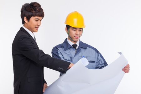 asian architect: Asian business man and engineer having a blueprint isolated on white.