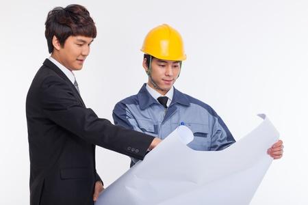 Aziatische zakenman en ingenieur die een blauwdruk geïsoleerd op wit.