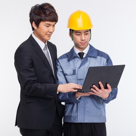 Business man en ingenieur die laptop op wit wordt geïsoleerd Stockfoto