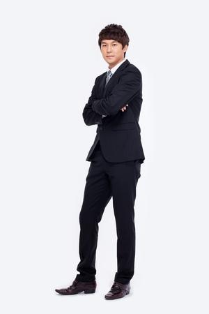 Jonge Aziatische bedrijfsmens die op witte achtergrond wordt geïsoleerd. Stockfoto
