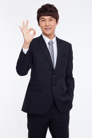 ok hand: Young Asian business man showing okay sign isolated on white background.
