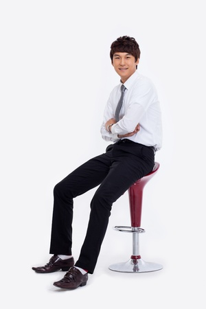 executive chair: Young Asian business man sitting on the chair isolated on white background.  Stock Photo