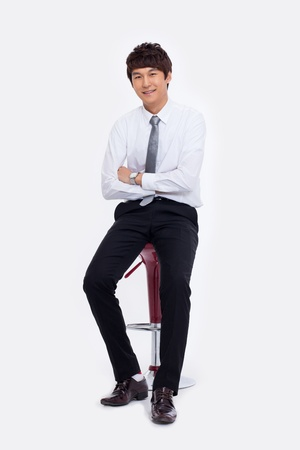 Young Asian business man sitting on the chair isolated on white background.  Stock Photo - 18471566