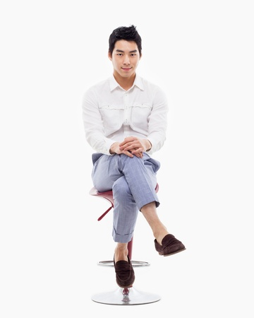 Young Asian person sitting on the chair isolated on white. Фото со стока