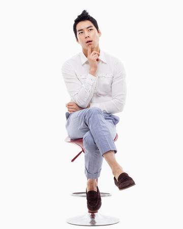 Jonge Aziatische mens het denken over de stoel geïsoleerd op witte backgroung. Stockfoto
