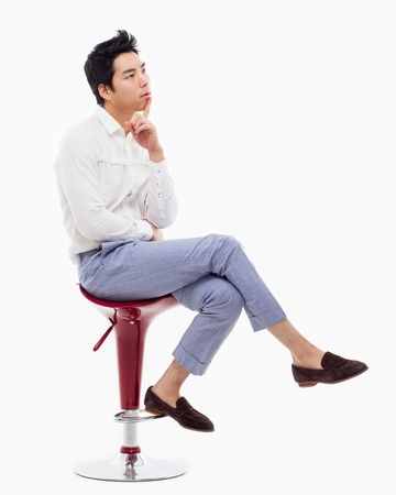 seated: Young Asian man thinking on the chair isolated on white backgroung.  Stock Photo
