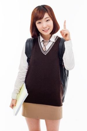 Jonge mooie Aziatische student aangeven ruimte, geïsoleerd op een witte achtergrond.