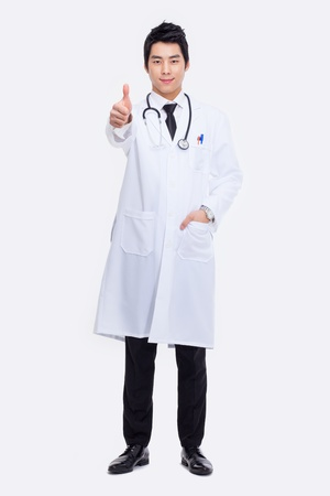 Young Asian doctor showing thumb isolated on white background. photo