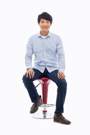 personas sentadas: Persona asiática joven que se sienta en la silla aislada en blanco.