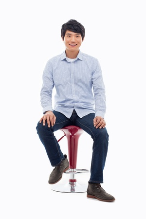 man in chair: Young Asian person sitting on the chair isolated on white. Stock Photo