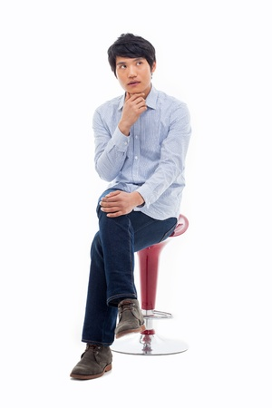 1 person: Young Asian man thinking on the chair isolated on white backgroung.  Stock Photo