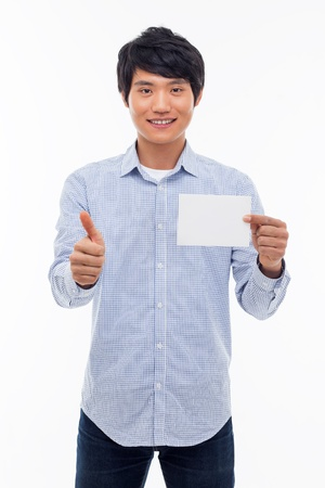 Young asian man showing empty card and showing thumb isolated on white background.  photo