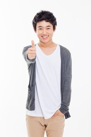 good looks: Young Asian man showing thumb isolated on white background.