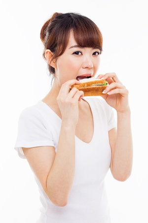 woman eat: Young Asian woman eat sandwhich ioslated on white.