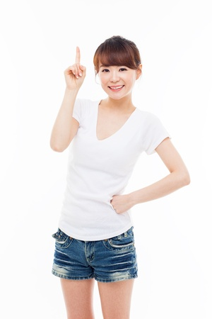 woman pointing up: Smiling young woman pointing upwards isolated on white background