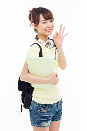 Young happy Asian student show OK sign isolated on white.