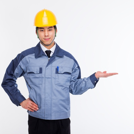 Young Asian engineer show something isolated on white. Stockfoto