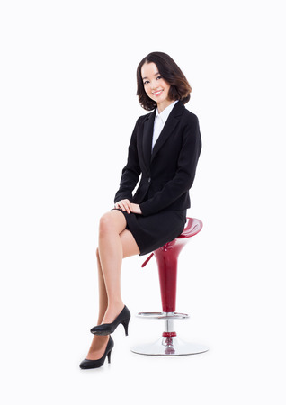 young woman sitting: Young Asian business woman sitting on the chair isolated on white