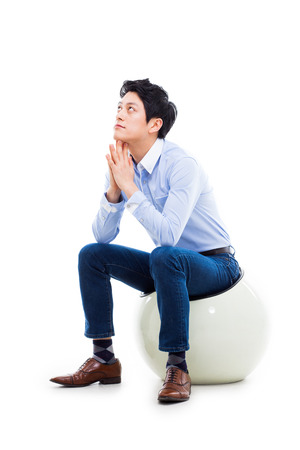 Young Asian man thinking on the chair isolated on white backgroung.  photo