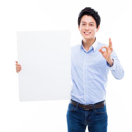 若いアジア男が白い背景で隔離パンネル カードを示します。