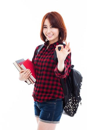 Joven estudiante asiático feliz mostrará OK signo aislado en blanco.